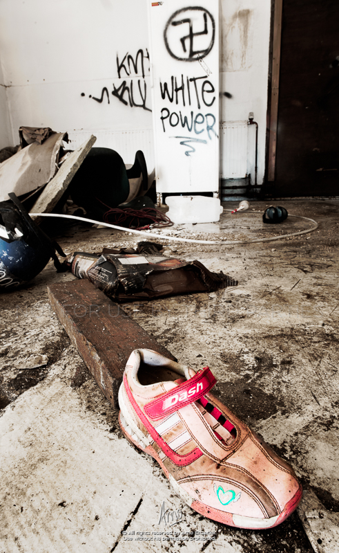 "There's a weird juxtaposition in this image. This was in the entrance of a burnt house. The hallway was filled with water, the walls were black with charcoal. On the wall the nazi symbol and the slur ""White Power"" in black on the only white wall left in the house. And that little heart on the sneaker."